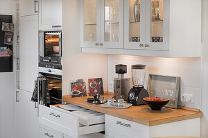 Glass-fronted wall units in white fitted kitchen