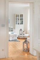 Blick ins Wohnzimmer mit hellem Holzdielenboden und weißen Möbeln in umgebauter Molkerei