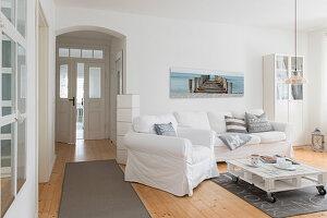 Sitzmöbel mit weißen Hussen, Paletten-Couchtisch und heller Holzdielenboden im Wohnzimmer, in umgebauter Molkerei