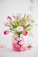 Easter bouquet in glass vase full of Easter eggs