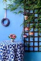 Blumenstrauss in kleinem Eimer auf Tisch, darüber Kranz und Rankgitter mit DIY-Windlichtern