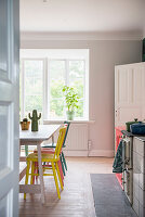 View into kitchen with colourful chairs around table in front of large window