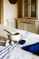 Pestle and mortar and eggs on rough linen cloth with three blue stripes