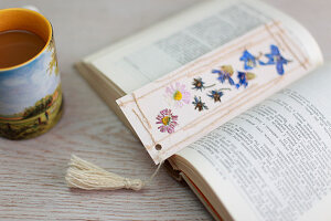 Bookmark decorated with pressed flowers, threads and tassel