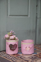 Flowers and tealight in vases with hand-sewn fabric covers