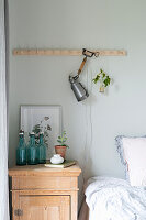 Clip-on lamp on row of pegs above bed and old bedside cabinet