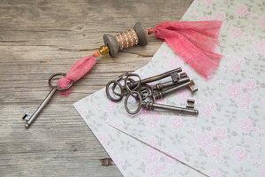 Schlüsselanhänger aus einer Garnrolle und bunte alte Schlüssel