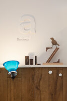 Blue clip-on lamp on wainscoting