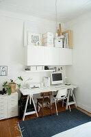 Weißer Schreibtisch, weißer Hängeschrank und Schubladencontainer in Zimmerecke