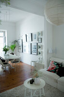 Scatter cushions on sofa and round side table in front of dining area with collection of pictures on wall