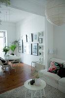 Sofa mit Kissen und runder Beistelltisch, im Hintergrund Essbereich mit Bildersammlung an der Wand