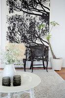 Runder, weißer Beistelltisch, im Hintergrund zwei Stühle vor Wandposter im Wohnzimmer