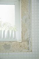 weiße Blumenvasen mit Schleierkraut auf Fensterbank
