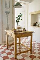 Alter Schubladentisch auf Schachbrett-Fliesenboden in der Küche