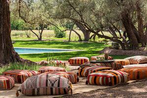 Gestreifte Bodenkissen im Olivengarten mit Pool