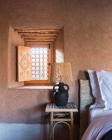 Tischleuchte aus einem Krug vor kleinem Fenster in der Lehmwand