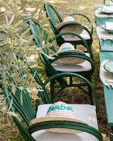Bestickte Strohhüte auf den grünen Gartenstühlen am Tisch