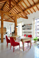 Red upholstered chairs around old wooden table in open-plan interior