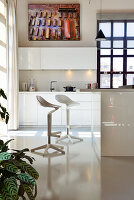 Bar stools in white kitchen with glossy cabinets