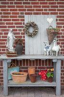 Holztisch mit verschiedenen Dekoobjekten un Blumentöpfen an Ziegelwand