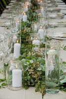 Festlich gedeckte Tafel mit Windlichtern und Blumengirlande