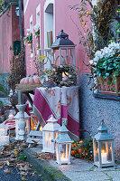Laternen mit Herbstdeko an Hauswand arrangiert