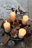 Lit candles on plate with fabric flowers and paper snowflakes
