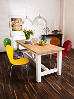 Colourful modern chairs around wooden country-house-style table