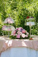 Romantischer Tisch im Garten mit Blumenschmuck und Tortenfuß