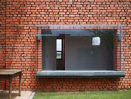 Window seat in modern bay window in old brick wall
