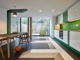 Modern kitchen-dining room with green accents and graphic details