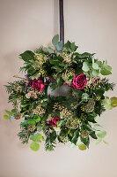 DIY-Weihnachtskranz mit Rosenblüten an der Wand