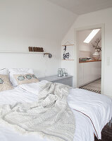 Double bed in white bedroom with view into hallway