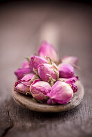 Dried rose buds on wooden spoon (close-up)