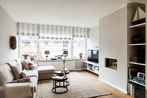Pale sofa set, set of tables, TV, gas fire and shelves in living room