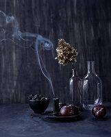 Stillleben mit ausgepusteter Kerze, Herbstfrüchten und Trockenblüten in Vase