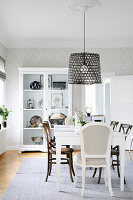 Table and display cabinet in grey-and-white dining room