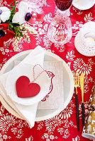 Festliches Gedeck mit Herzdekoration auf rot-weisser Tischdecke