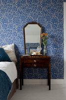 Alter Spiegel und Nachttisch vor blau geblümter Tapete