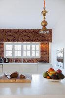 Obstschale in moderner Küche mit gemusterten Fliesen in Gold