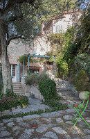Grüner Gartenstuhl im Hof eines mediterranen Steinhauses