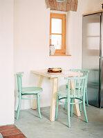 Kleiner Frühstückstisch und mintfarbene Stühle