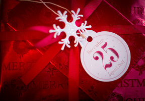Christmas present wrapped in red paper with tag