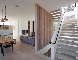 Open-plan staircase in modern architect-designed house with pale wooden elements