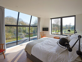 Floor-to-ceiling glass wall in bedroom overlooking garden