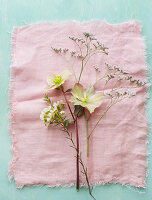 Flowers on pink cloth (hellebore, sea lavender, waxflower)