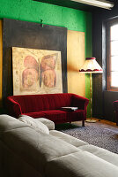 Red velvet sofa below large artwork on wall and pale leather sofa in renovated loft apartment
