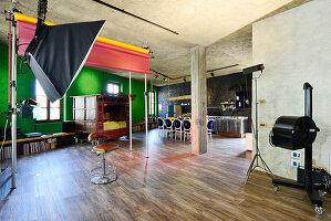 Fotografenlampe und Hocker, im Hintergrund antikes, chinesisches Bett in renoviertem Loft