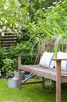 Cushions on garden bench in idyllic summer garden