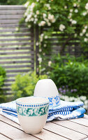 Two cups with green and blue patterns on garden table
